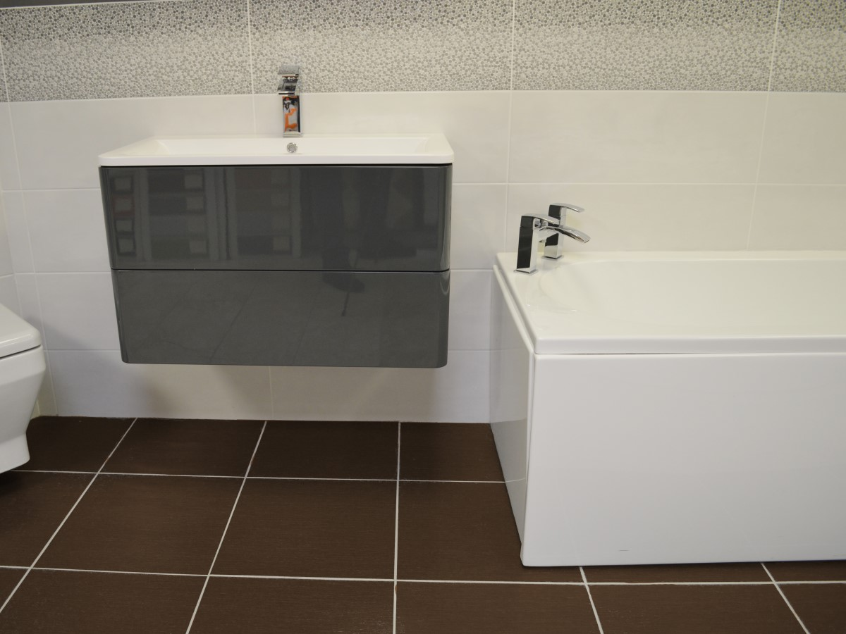 bathroom featuring a stand alone basin unit & brown floor tiles