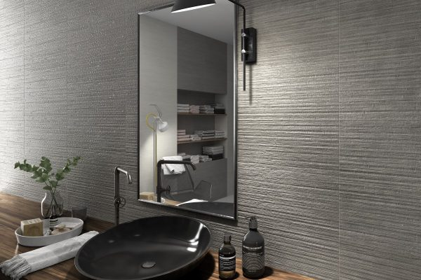 fresh black freestanding basin on a workbench with rivened grey wall tiles
