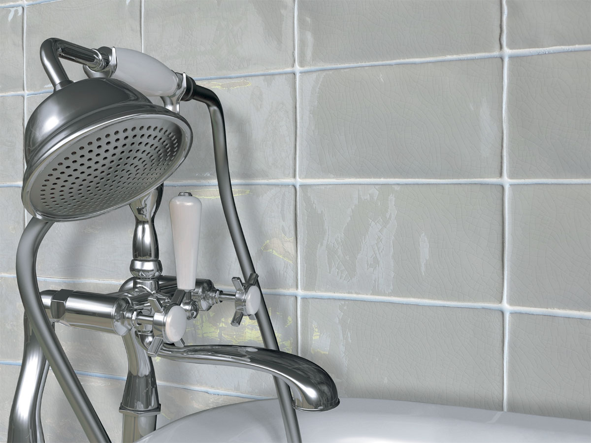 up close of a traditional bath tap with crackle tiles behind