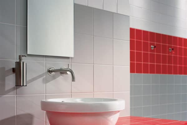 functional bathroom with vibrant red tiles as a border
