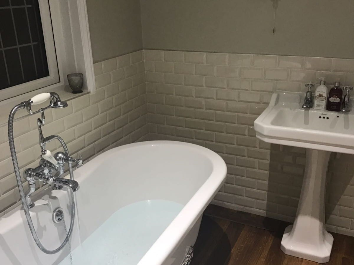 traditional feeling bathroom with a freestanding bath and white bevel tiles