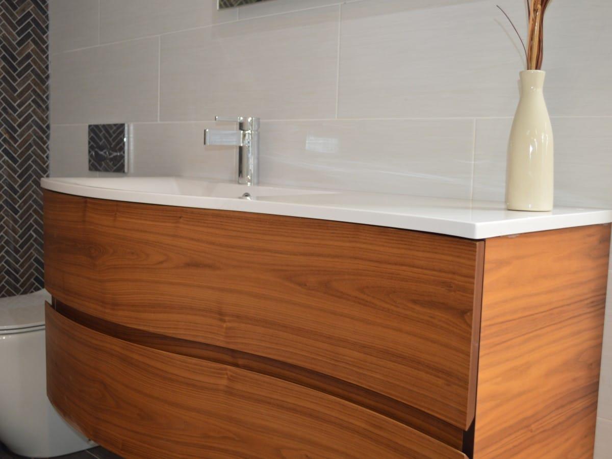 stylishly curved basin unit in a walnut finish