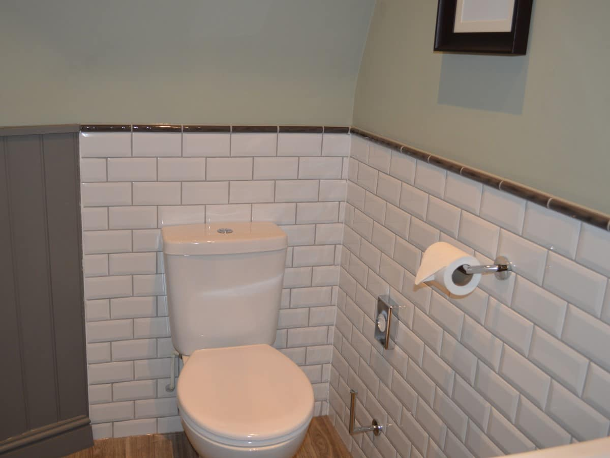 Bevelled white tiles used half height in a bathroom redesign