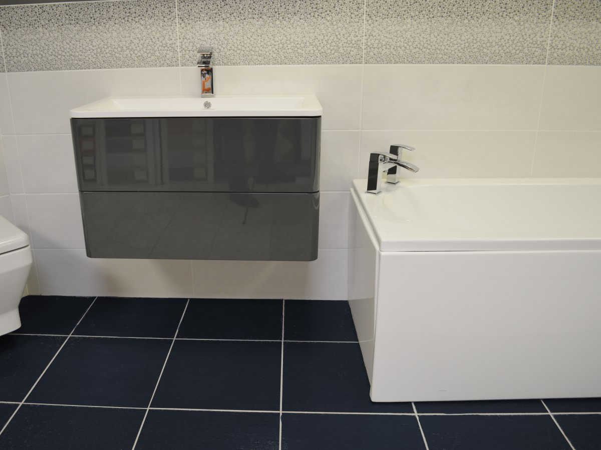 bathroom featuring a stand alone basin unit & black floor tiles