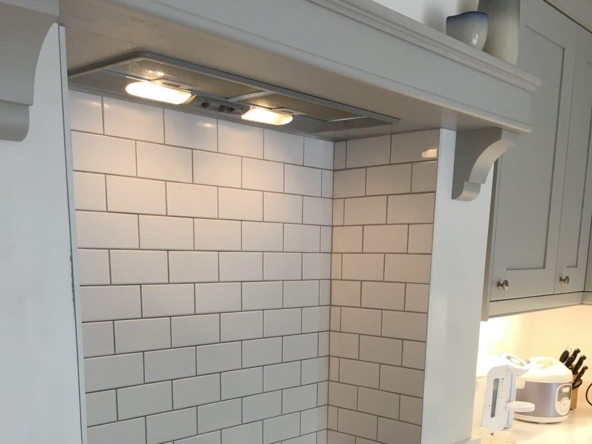 enclosed cooker hood splashback using white metro tiles