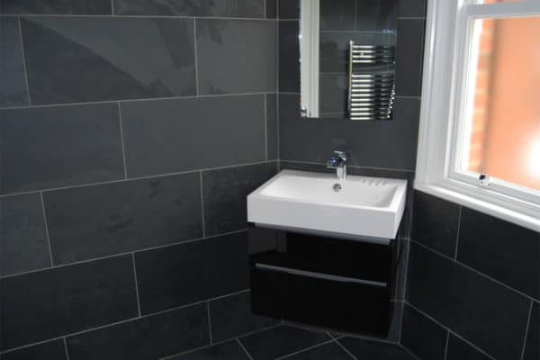 slate tiled bathroom with a wall hung basin & unit in gloss black