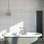 free standing traditional bath with white brick effect tiles