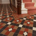 victorian floor tiles in a hallway using red, brown and black colours